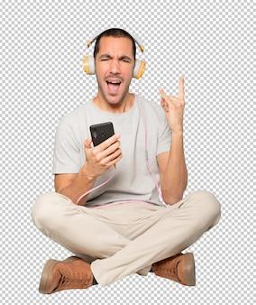 Młody mężczyzna w pozycji siedzącej z rockowym gestem