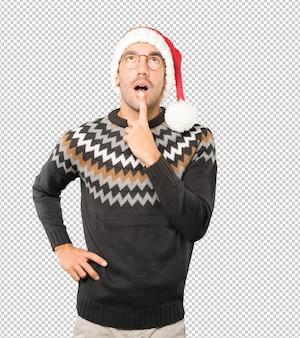 Młody mężczyzna w świątecznym kapeluszu podczas gestykulacji odizolowywającej