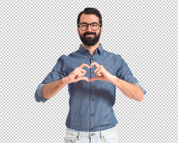 Młody modnisia mężczyzna robi sercu podpisywać