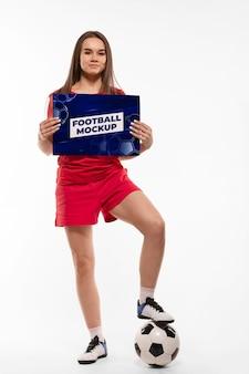 Młody piłkarz pokazujący makietę urządzenia cyfrowego