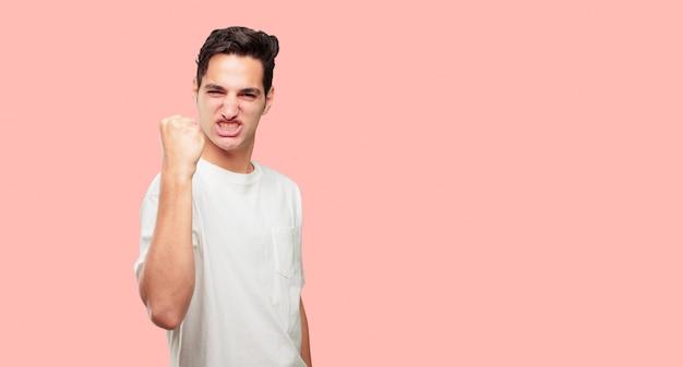 Młody przystojny mężczyzna gesturing victory, with a happy, proud and satisfied look on face