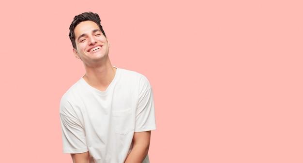 Młody przystojny mężczyzna laughing out loud z głową przechyloną do tyłu i szczęśliwy, wesoły wypowiedzi