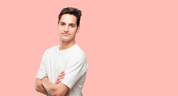 Młody przystojny mężczyzna stoi bokiem, z dumnym, zadowolonym i szczęśliwym wyrazem twarzy