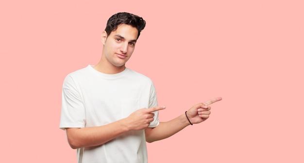 Młody przystojny mężczyzna uśmiecha się i wskazując na bok obiema rękami