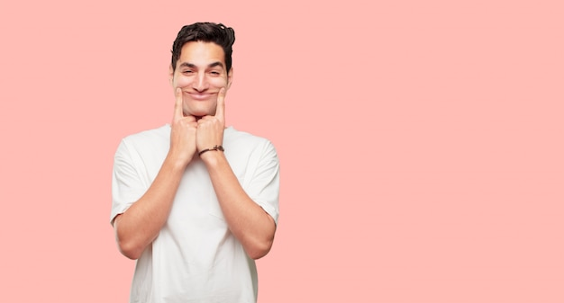 Młody przystojny mężczyzna wymuszający uśmiech na twarzy obiema palcami wskazującymi