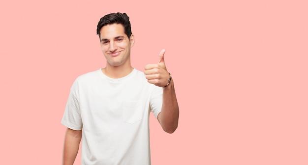 Młody przystojny mężczyzna z zadowolony, dumny i szczęśliwy wygląd z kciuki w górę