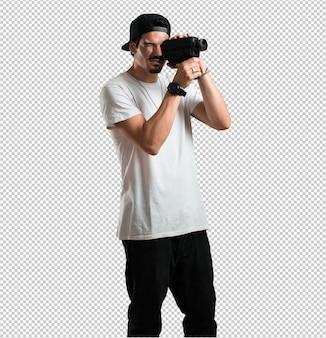 Młody raper człowiek podekscytowany i zabawny, patrząc przez kamerę filmową