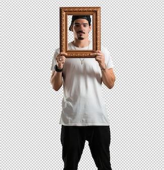 Młody raper człowiek uśmiechnięty i zrelaksowany, patrząc przez ramki, śmieszne i kreatywne zdjęcie
