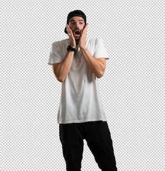 Młody raper człowiek zaskoczony i zszokowany, patrząc z szeroko otwartymi oczami
