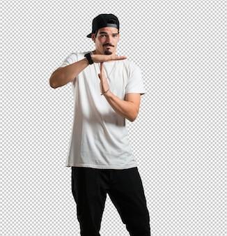 Młody raper mężczyzna zmęczony i znudzony, wykonując gest przekroczenia limitu czasu, musi się zatrzymać z powodu stresu w pracy, pojęcie czasu