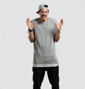 Młody raper śmieje się i bawi, jest zrelaksowany i wesoły, czuje się pewnie i odnosi sukcesy