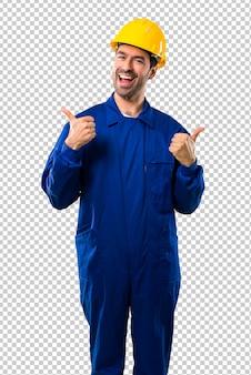 Młody robociarz z hełmem daje aprobata gestowi z oba rękami i ono uśmiecha się