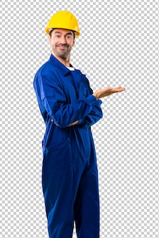 Młody robociarz z hełmem przedstawia produkt lub pomysł podczas gdy patrzejący uśmiecha się w kierunku