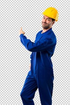 Młody robociarz z hełmem wskazuje z powrotem z palcem wskazującym przedstawia produkt od behind