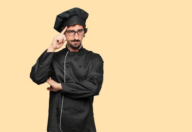 Młody szalony człowiek jako szef kuchni koncentrując się mocno na idei, z poważnym, dalekim spojrzeniem