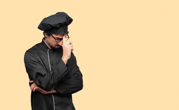 Młody szalony człowiek jako szef kuchni koncentrując się mocno na idei, z poważnym spojrzeniem