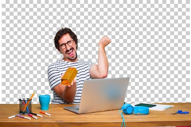 Młody szalony grafik na biurku z laptopem iz sztabki złota