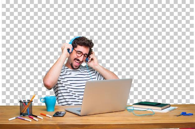 Młody szalony projektant graficzny na biurku z laptopa i słuchanie muzyki za pomocą słuchawek