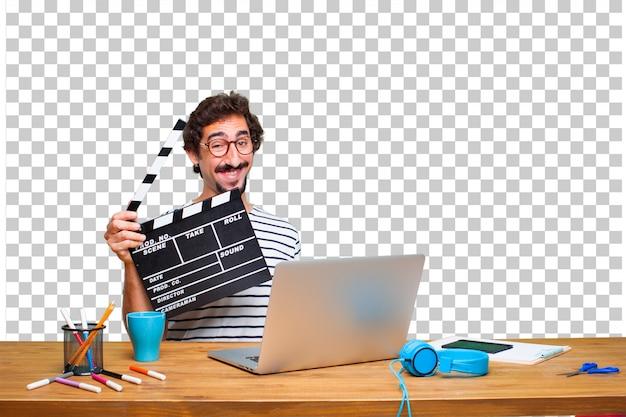 Młody szalony projektant graficzny na biurku z laptopem iz kino klakier