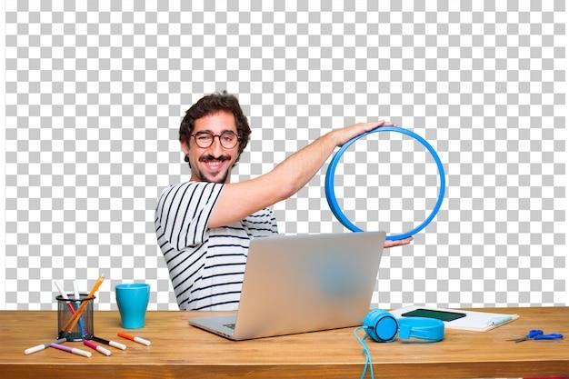 Młody szalony projektant graficzny na biurku z laptopem iz ramą
