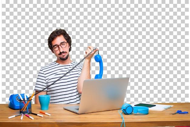 Młody szalony projektant graficzny na biurku z laptopem iz rocznika telefonu