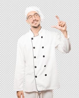Młody szef kuchni robi gest małego rozmiaru ręką