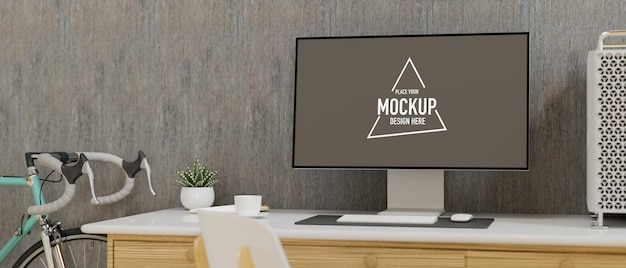 Monitor komputerowy z ekranem makiety na biurku w domowym biurze z rowerem