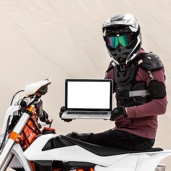 Motocyklista trzymając laptopa