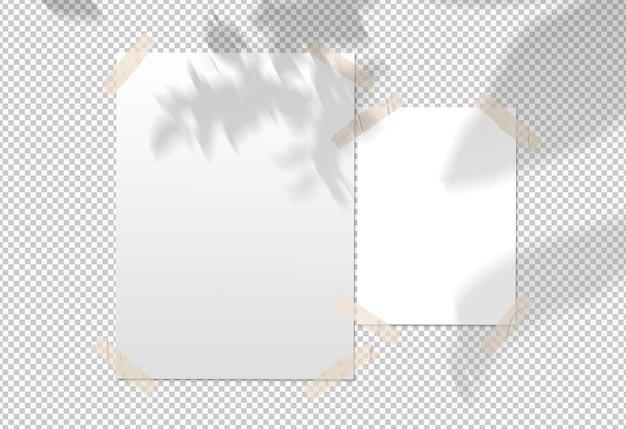 Na białym tle paczka białych plakatów z taśmą i cieniem