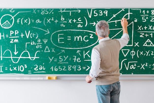 Nauczyciel pisze formuły matematyczne na pokładzie
