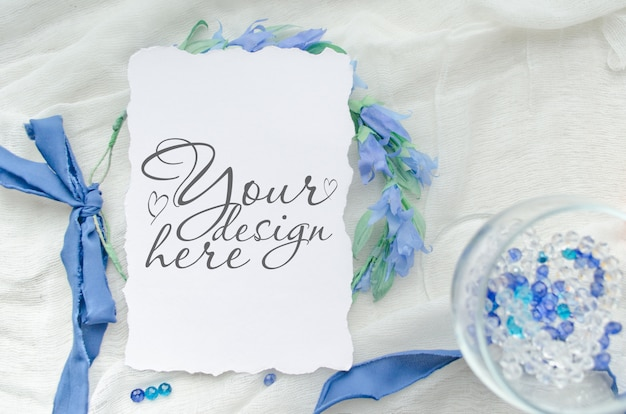 Niebieska makieta zaproszenia ślubne ozdobiona jedwabną wstążką, kryształami i wieńcem panny młodej