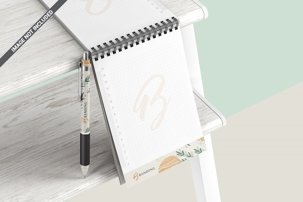 Notatnik z długopisem na drewnianej półce makieta marki