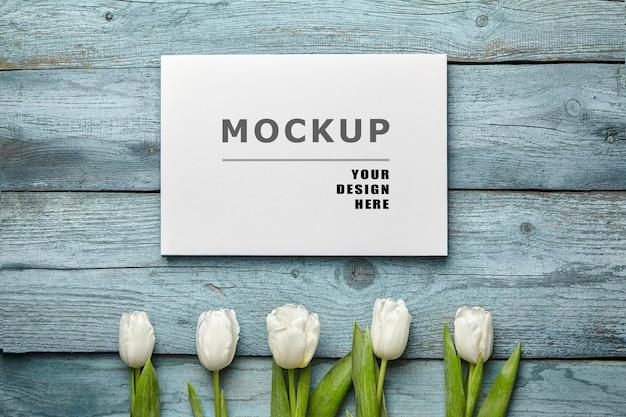 Obraz na płótnie makieta i białe kwiaty tulipanów na niebieskiej drewnianej powierzchni leżącej płasko