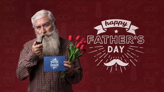 Ojciec trzyma kartonowe makiety i kwiaty na bordowym tle