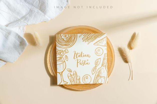 Okrągły złoty talerz z makietą menu i suchą rośliną.