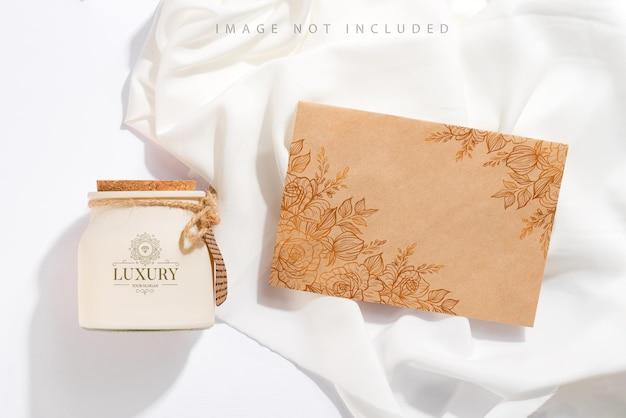 Organiczna zapachowa świeca sojowa z etykietą, papierem rzemieślniczym i cieniem na białej tkaninie. opakowanie makiety