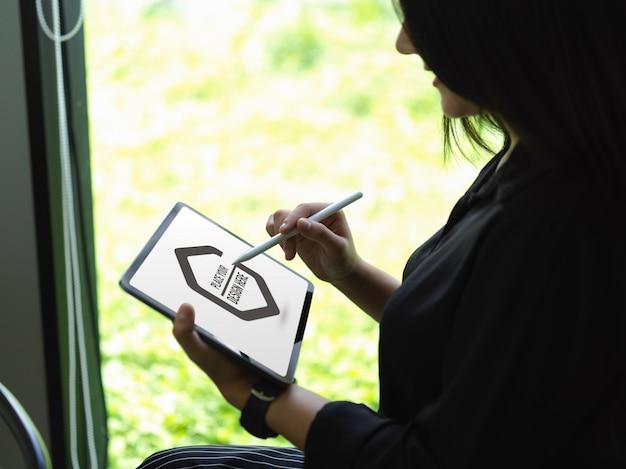 Osoba korzystająca z makiety cyfrowego tabletu, siedząc na fotelu w pobliżu szklanego okna