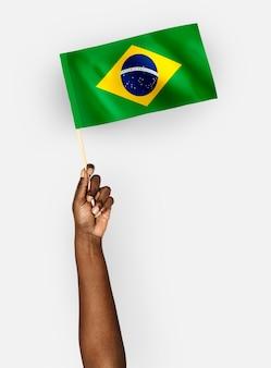 Osoba machająca flagą federacyjnej republiki brazylii