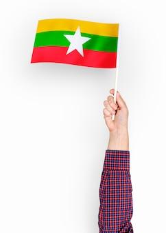 Osoba machająca flagą republiki związku myanmar