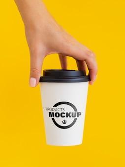 Osoba trzyma makietę białej filiżanki kawy
