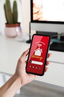 Osoba trzymająca smartfon z aplikacją automatyki domowej