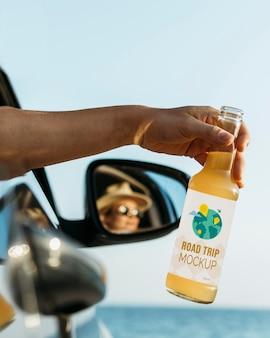 Osoba w samochodzie trzymająca makietę butelki