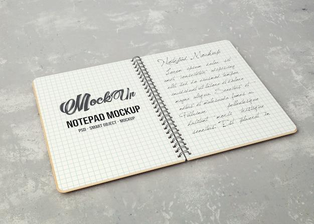 Otwarty notatnik z makietą w białej kartce