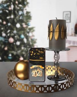 Ozdoby na tacy obok telefonu z wiadomością na nowy rok
