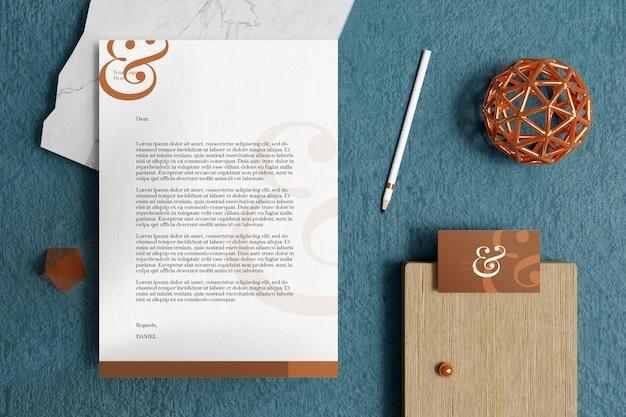 Papier firmowy a4 z wizytówką i makietą materiałów biurowych w niebieskim dywanie