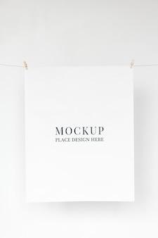Papierowe makiety psd zwisające z liny ze spinaczami do papieru