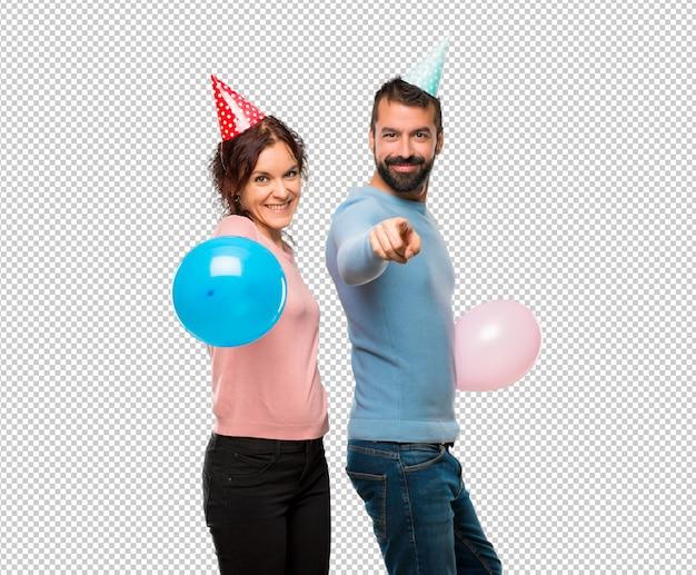 Para z balonami i czapkami urodzinowymi wskazuje palcem na ciebie z pewnym siebie wyrazem