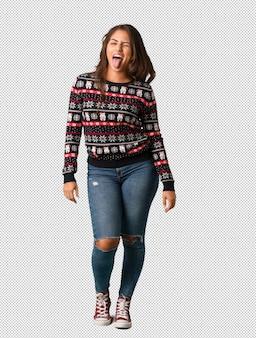 Pełna ciało młoda kobieta ubrana w boże narodzenie jersey funnny i przyjazny pokazując język