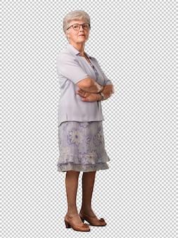 Pełne ciało starszej kobiety przekraczającej jego ramiona, poważnej i imponującej, czującej się pewnie i pokazującej siłę
