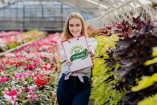 Piękna młoda dziewczyna trzyma eco życzliwego znaka